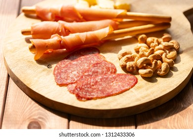 Cashew nuts, salami and turkey bacon with grissini on wooden plate. Selective focus.