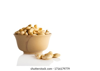 Cashew nuts in a white bowl on a white background