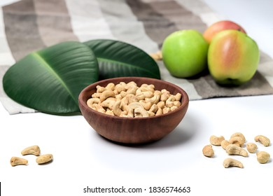 Cashew nuts in a wooden bowl, green leaves and apples isolated on white background. Clipping path stil photo