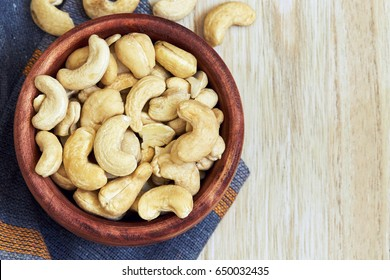 Cashew nuts in wooden bowl. Top view with copy space