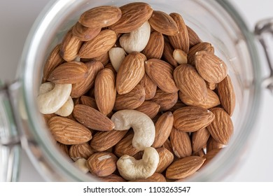 Cashews and almonds in a glass jar.
