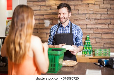Cashier and customer smiling face to face while buying groceries at a supermarket