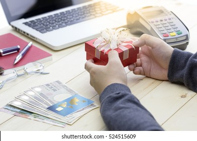 Cashier hand holding a Christmas gift with credit card over Japanese bank notes and EDC machine or credit card terminal. This is fake credit card.