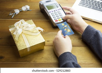 Cashier hand holding a Credit card over EDC machine or credit card terminal with golden christmas gift box.