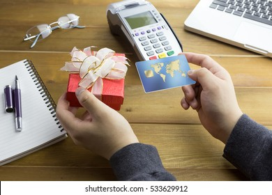 Cashier hand holding a Credit card over EDC machine or credit card terminal with christmas gift. This is fake credit card.