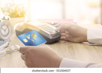 Cashier hand holding a Credit card over EDC machine or credit card terminal to made a payment on his desk. This is fake credit card.
