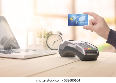 Cashier hand holding a Credit card over EDC machine or credit card terminal. This is fake credit card.