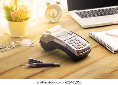 Cashier hand holding a Credit card over EDC machine or credit card terminal with calculator and glasses.