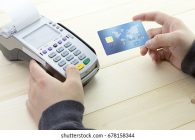 Cashier hand holding a Credit card over EDC machine or credit card terminal with calculator and glasses. This is fake credit card.