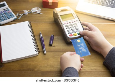 Cashier hand made a payment with Credit card and EDC machine or credit card terminal with calculator and glasses. Warm toning effect. This is fake credit card.