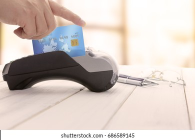 Cashier hand over EDC machine or credit card terminal to made an online payment. This is fake credit card.