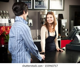 Cashier helping a customer at a cafe