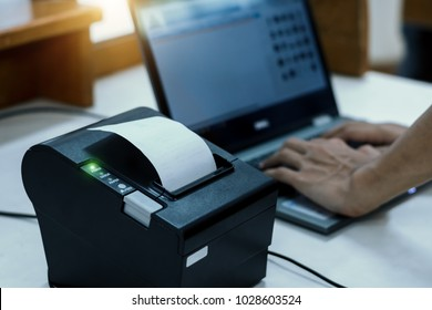 Cashier are recording sales data on notebook with thermal receipt printer at counter service.For mockup and advertising.The concept of trading business.Receipts and invoices