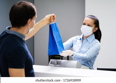 Cashier In Retail Shop Or Store At Counter Wearing Face Mask