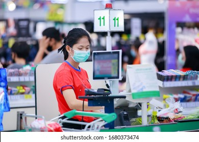 Cashier or supermarket staff in medical protective mask working at supermarket.covid-19 spreading outbreak