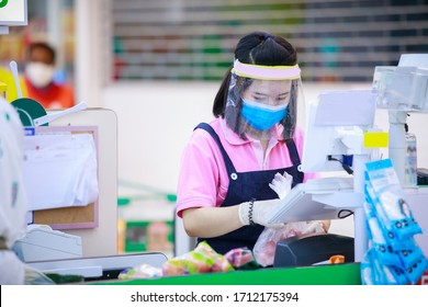 Cashier or supermarket staff in medical protective mask and DIY face shield working at supermarket. covid-19 spreading outbreak