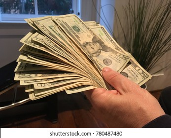 Cashing Out of Startup Business Concept - Holding Pile of Cash