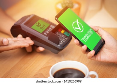cashless Society, customer paying bill through smartphone using NFC technology at point of sale terminal in cafe. mobile digital wallet technology concept