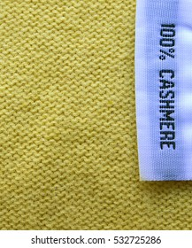 Cashmere texture.Cashmere textile background.100% Cashmere wool texture.Fabric label on yellow cashmere background.Selective focus.
