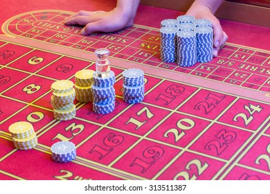 Casino American Roulette gambling table with a playing chips on the layout. Croupier is doing payout.