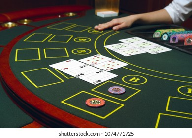 Casino black jack table with chips and cards. Winning combination. Hand of Croupier behind gambling table.