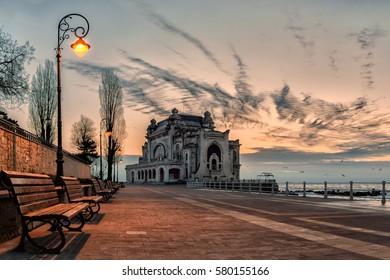The Casino building in Constanta on the promenade of the Black Sea coast with lit street light. Casino Constanta, Romania.
