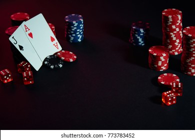 Casino chips and cards on black table surface. Gambling, fortune, game and entertainment concept - close up