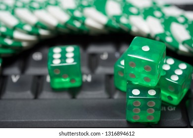 Casino chips and dices stacking on a laptop.