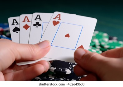 Casino chips and four of kind poker combination in a woman's hand.