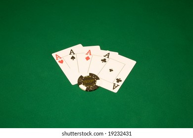 Casino chips on the green table and four aces
