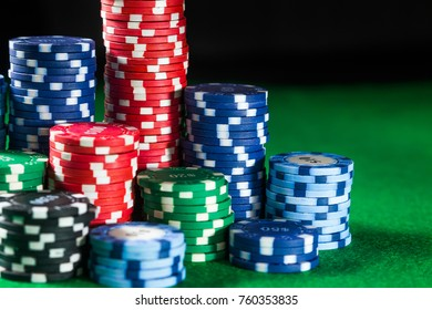 of casino chips on green table surface. gambling, fortune, game and entertainment concept - close up