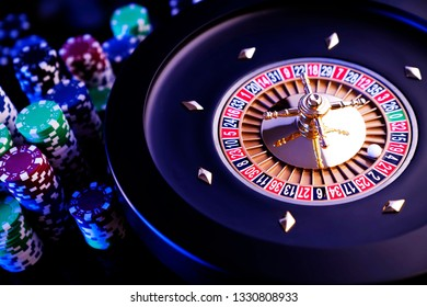 Casino concept. High contrast image of casino roulette, poker chips, cards, dice on gaming table. Bokeh background.