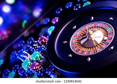 Casino concept. High contrast image of casino roulette, poker chips, cards, dice. Bokeh background.