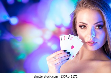 Casino concept. Portrait of young attractive woman, playing in casino. Poker chips, cards, roulette wheel, bokeh background.