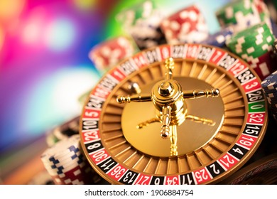 Casino and gambling concept. Roulette wheel, poker chips, dice, cards on colorful bokeh background