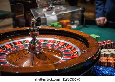 Casino, gambling and entertainment concept - roulette table and stack of poker chips
