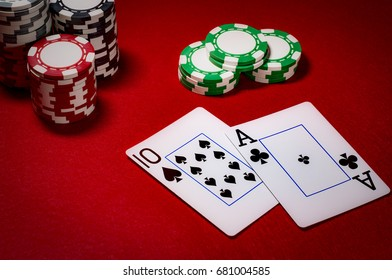 Casino gambling and gaming industry concept with cards making a blackjack surrounded by chips and a 3 to 2 payout in dim lights