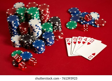 Casino gambling poker equipment and entertainment concept - close up of playing cards and chips at red background. Flush