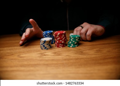 casino, gambling, poker, people and entertainment concept - close up of poker player with chips at casino table. Gambler man hands pushing large stack of colored poker chips across gaming table