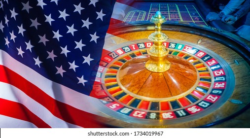 Casino. Gambling in the United States. Roulette on the background of the flag of the United States of America. Money games in America. Roulette and American flag close-up.