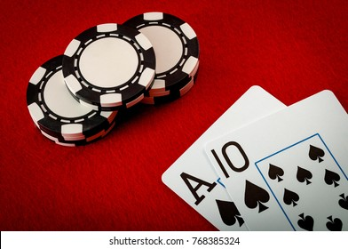 Casino games, addiction to gambling and the gaming industry concept with an ace and a ten next to chips representing the payout for a blackjack on a red felt background, Blackjack pays 3 to 2