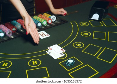 Casino pocker table with chips and cards. Winning combination. Hand of Croupier open cards.