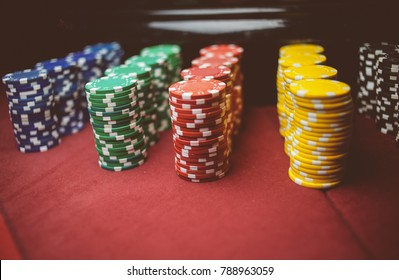 Casino / poker chips colorful gaming pieces lie on the game table in the stack. Background for gambling / casino, business, poker. many colorful casino chips. vintage photo processing. Soft focus
