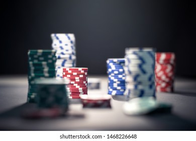 Casino poker chips in dramatic dark shadow or at night in spotlight. Stack of game money. Risk, luck and betting concept. Gambling problem and addiction.