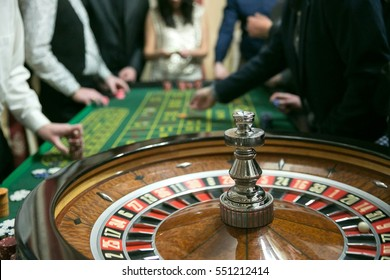 Casino roulette with people making bets in background