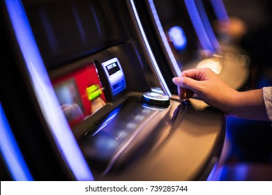 Casino Slot Machine Games Playing. Woman Hand on the Machine Bet Button. Closeup Photo
