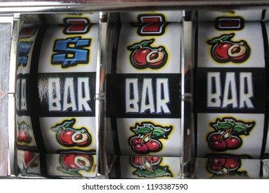 Casino slot machine, one-armed machine or fruit machine. Jackpot of triple bar on reels spins.