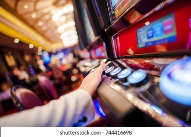 Casino Slot Video Games. Woman Playing Video Slot in the Casino. Hand on Betting Button Closeup Photo.
