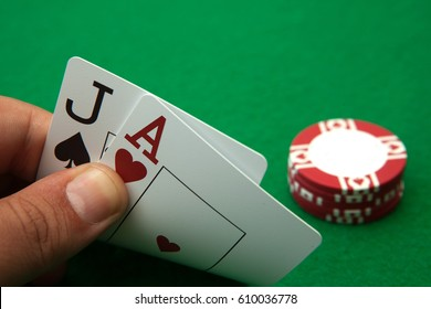 Casino table with cards showing black jack hand and blurred casino chips in the background