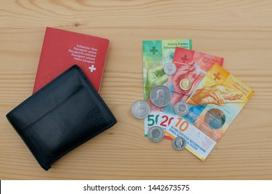 Caslano, Ticino, Switzerland - 3rd July 2019 : Top view of a black wallet Swiss passport and currency on a wooden table